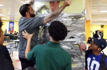 Students and Staff taping Principal Fucheck to the wall